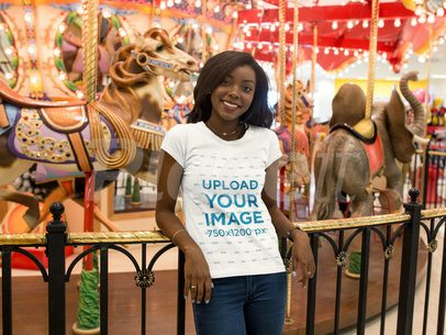 Mockup of a Young Woman Wearing a T-shirt  While Happily Standing Against a Carousel 16044