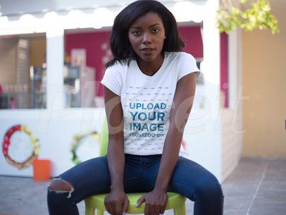 T-shirt Mockup Featuring a Young Woman Wearing a Round Neck Tee While Sitting Down Outdoors a16055