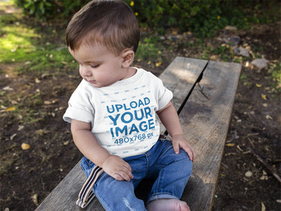 Mockup of a Baby Boy Looking Down to the Floor While Wearing a Tshirt a16086