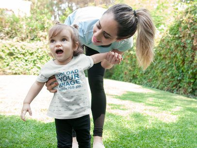 Mockup of a Smiling Baby Girl Wearing a T-shirt with Her Mom a16097