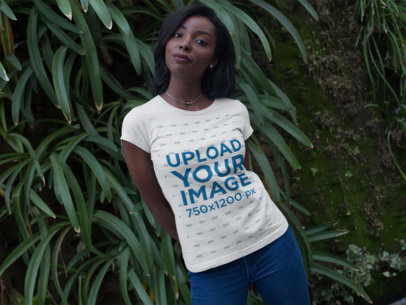 Young Black Girl Wearing a T-Shirt Mockup While Standing Against a Big Plant a16065
