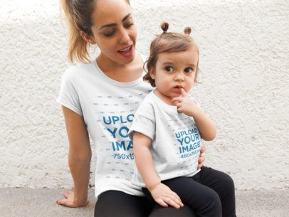 Mockup of a Mother with Her Baby Girl Wearing T-Shirts While Sitting a16098