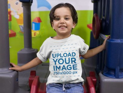 Mockup of a Little Happy Boy Wearing a Tshirt While Having Fun in the Playground a16137