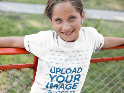 Smiling Little Girl Wearing a T-Shirt Mockup While Lying Against a Red Railing a16170