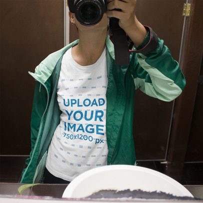 Mockup of a Girl Taking a Selfie with a Camera in a Bathroom While Wearing a T-Shirt Mockup and a Green Jacket a16214
