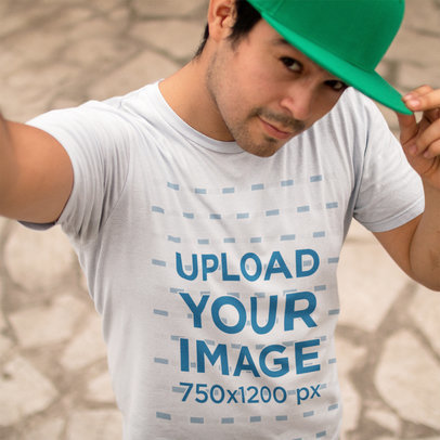 Young Man Wearing a Round Neck Tee Mockup and a Hat While Taking a Selfie a16227