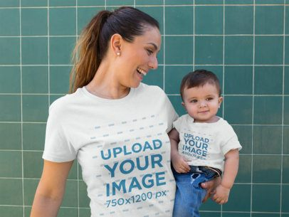 Baby Boy and his Mom Wearing Different Round Neck Tees Mockup while Against a Green Tiles Wall 16095
