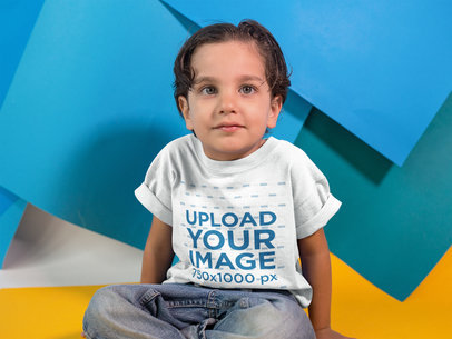 Little White Kid Wearing a Round Neck Tee While Sitting in a Studio a16145