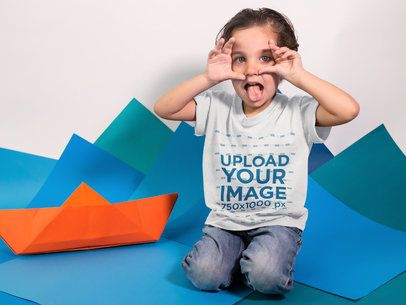 Kid Doing a Funny Face While Wearing a T-Shirt Mockup in a Studio a16141