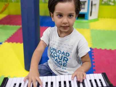 Kid Playing the Piano While Wearing a Round Neck Tee Mockup a16148
