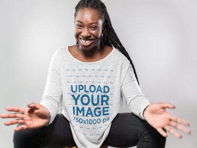 Smiling Woman Wearing a Long Sleeve Heather Off Shoulder Tshirt Mockup Sitting Down Against a White Background a16196
