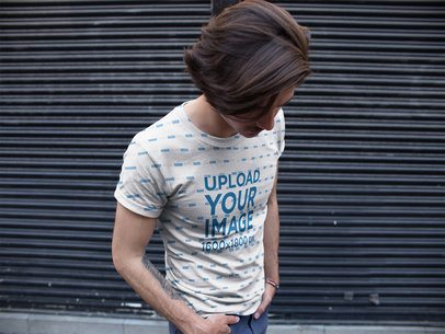 Young Dude Hiding his Face While Wearing a Sublimated Tshirt Mockup Against a Gray Shutter a15365
