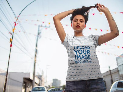 Hispanic Edgy Woman Wearing a Sublimated T-Shirt Mockup While Fixing her Hair in the Street a15422