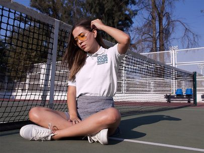 Mockup of a Young Girl Sitting Down in a Tennis Court While Wearing a Polo Shirt a15716