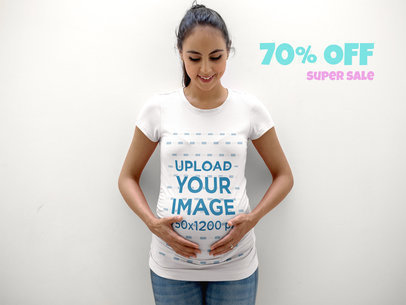Pregnant Mom Wearing a T-Shirt Template Lying Against a White Wall a16323