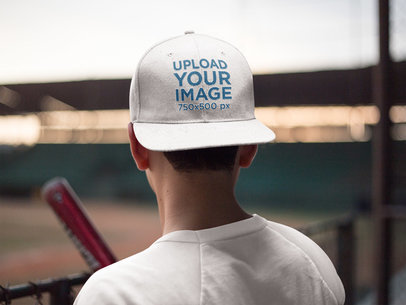 Young Baseball Player Watching the Field While Wearing a Hat Mockup a16182