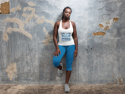 Runner Girl with Dreadlocks Wearing a Tank Top Mockup While Lying Against a Concrete Wall a16744