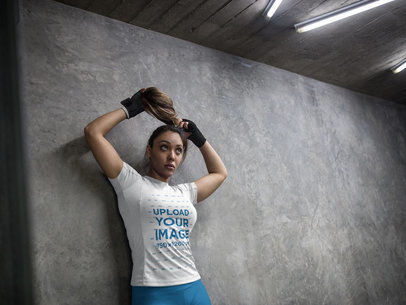 Woman Wearing Custom Sportswear Mockup and Boxfit Hand Gloves While Against a Concrete Wall a16841