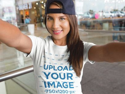 Selfie of a Girl Wearing a Hat and a T-Shirt Mockup While at the Mall a16914