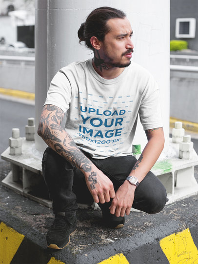 Tattooed Man Wearing a Round Neck Tee Mockup While Crouching Under a Bridge a17078