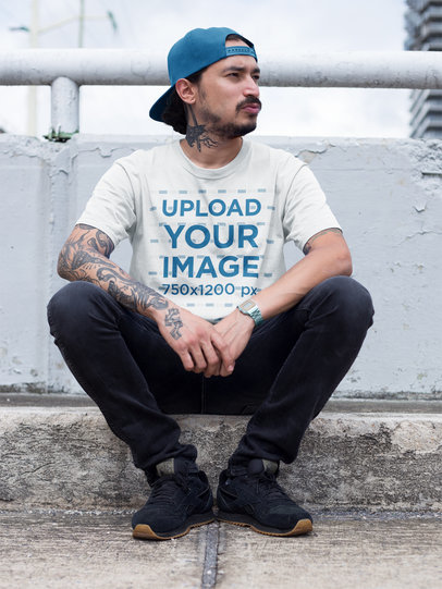 Mockup of a Tattooed Hispanic Man Wearing a Round Neck Tee While Sitting Down on a Sidewalk a17084