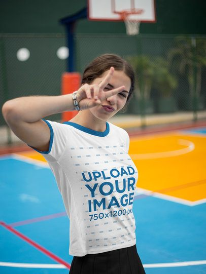 Girl Wearing a Ringer Tshirt Mockup at a Court While Doing a Peace and Love Sign a17060