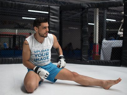 Man Stretching his Legs While Wearing Custom Sportswear Mockup Inside an MMA Cage a17042