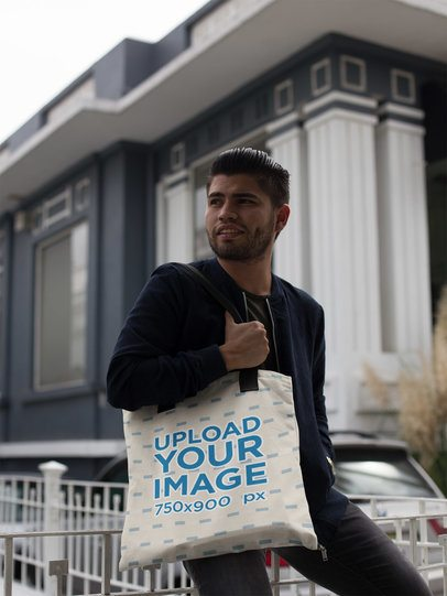 Happy Hispanic Man Carrying a Tote Bag Mockup while Sitting on a Fence a17088