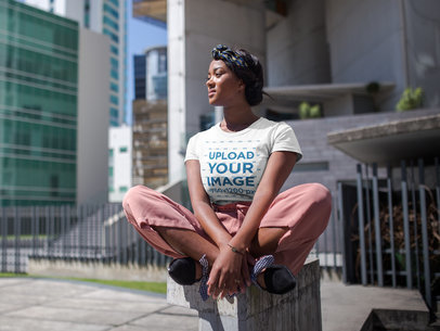 Beautiful Girl Wearing a Round Neck Tshirt Mockup While Sitting Near Corporate Buildings a17124