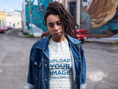 Woman with Dreadlocks Walking in the Middle of the Street Wearing a T-Shirt Mockup and a Denim Jacket a17139