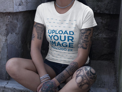 Cropped Face Girl Wearing a Round Neck Tee Mockup while Sitting at a Concrete Spot a17150