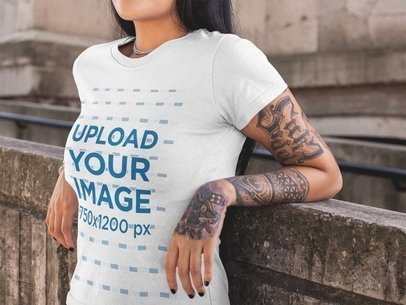 Mockup of a Tattooed Girl Wearing a Tee Mockup While Against a Concrete Church Wall a17171