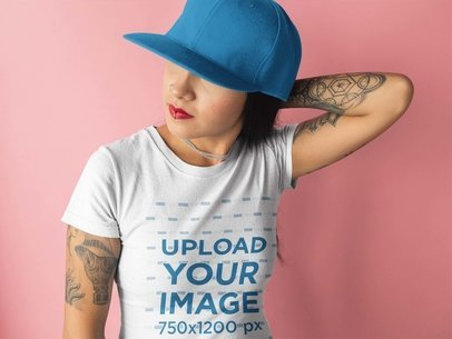 Tattooed Girl Wearing a T-Shirt Mockup and a Hat Against a Pink Background a17176