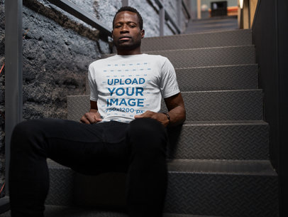 Black Man Sitting on Stairways While Wearing a Tshirt Mockup a17166