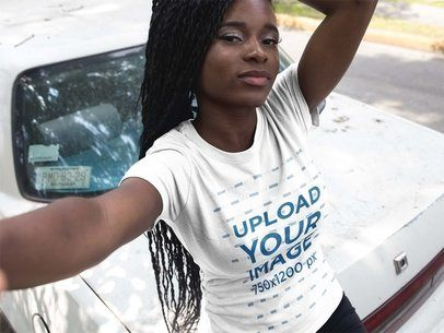 Selfie of a Pretty Black Girl with Dreadlocks Wearing a Round Neck Tee Mockup Next to an Old Car a17187