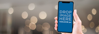 Mockup of an iPhone X Being Held Against a Blurry Background a17285