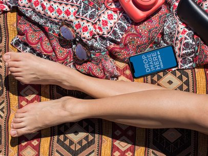 Mockup of an iPhone X Lying Next to a Sunbathing Womans Legs a17287