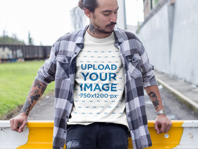 Man Wearing a T-Shirt Mockup and a Plaid Shirt While Outside the City a17081