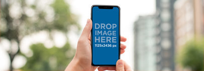 Mockup of an iPhone X Being Held While in the City a17294