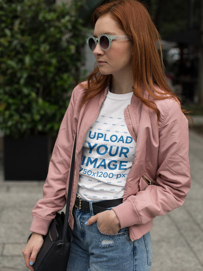 Fashion Girl Wearing a T-Shirt Mockup and a Pink Jacket While in the Street a17260