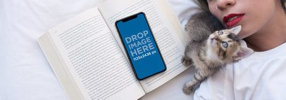 Kitten Next to an iPhone X Mockup Lying Over a Book on a Girls Bed a17384
