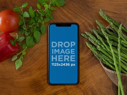 Mockup of a Space Gray iPhone X Lying on a Cooking Table a17382
