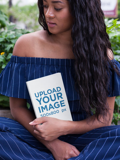 Beautiful Black Girl Holding a Book Mockup While at the Park a17332