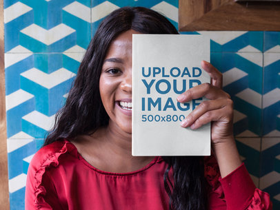 Black Girl Being Funny While Holding a Book Mockup Against her Face a17343