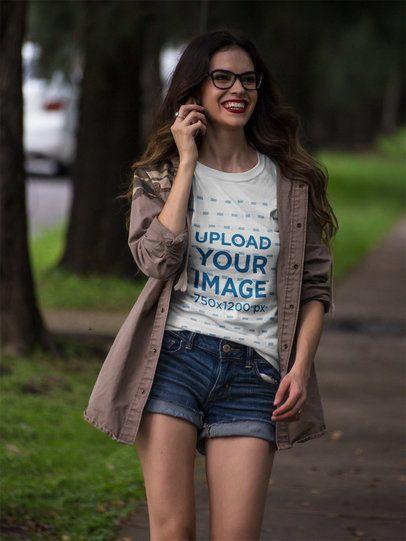 Happy Beautiful Girl Walking in the Park Wearing a T-Shirt Mockup a17359