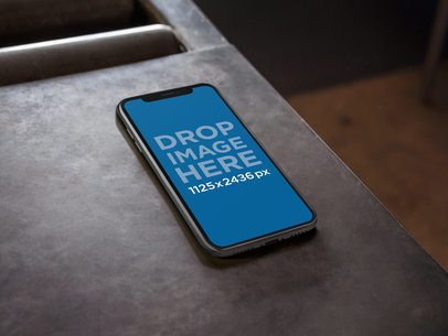 iPhone X Mockup Lying on a Metal Work Table a17481