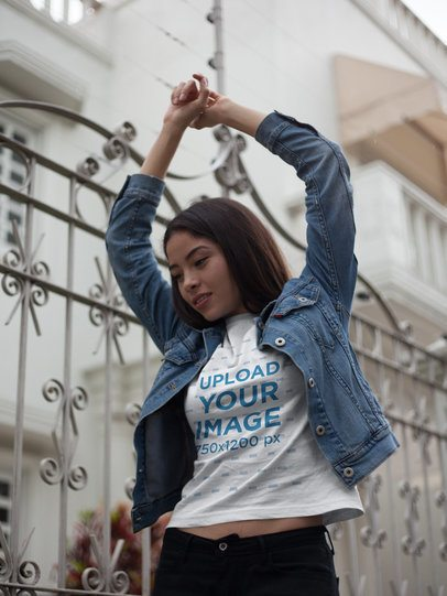 Asian Girl Wearing a Round Neck Tee Mockup and a Denim Jacket While Lifting her Arms Outdoors a17459