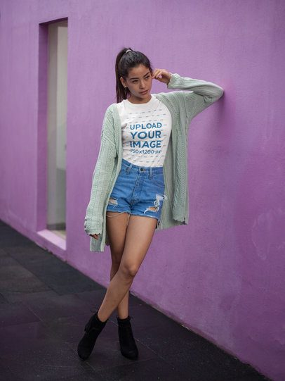 Pretty Asian Girl Wearing a T-Shirt Mockup While Against a Purple Wall a17477