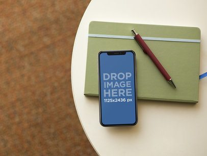 iPhone X Mockup Lying on a Table with a Notebook and a Pen a17540