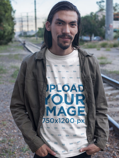 Smiling Man with Long Hair and Beard Wearing a T-Shirt Mockup on Train Rails a17594